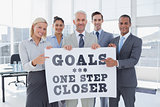 Composite image of business team holding large blank poster and pointing to it