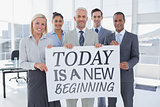 Composite image of business team holding large blank poster