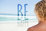 Composite image of young blonde man looking at the sea while sunbathing