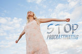 Composite image of young woman in summer dress stretching arms against sky