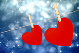 Composite image of hearts hanging on a line