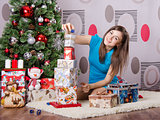 Girl near a Christmas tree collects from gifts pyramid