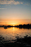 Beautiful Summer sunset landscape over low tide harbor with moor