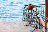 black bicycle with a basket near the fence on the pier