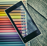 Cell phone  and crayons on wooden table background