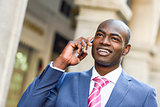 Black businessman talking with his smart phone in urban backgrou