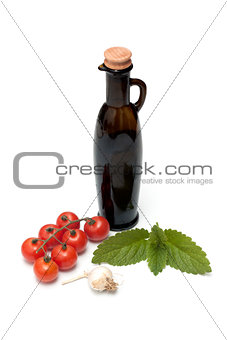 Tomatoes, olive oil, garlic and lime on white background