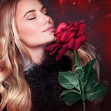 Beautiful woman smelling rose