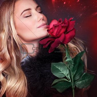 Beautiful woman smelling rose