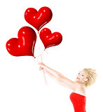 Happy girl flying, holding red heart balloons
