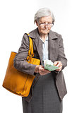 Senior woman counting money while standing over white background