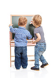 Toddler boys drawing on chalkboard over white background