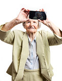 Happy elderly woman using touch screen mobile for taking selfie