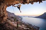 Seven-year old girl climbing a challenging route, father belaying. Kalymnos island, Greece