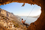 Male rock climber climbing on a roof in a cave, his partner belaying