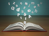 Open book with falling letters on green vintage background.