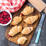 Fresh croissants with raspberries