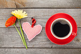 Cup of coffee, heart toy and gerbera flowers