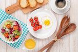 Healthy breakfast with fried egg, toasts and salad