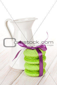 Green macarons with purple ribbon and milk jug