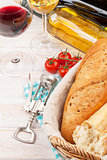 White and red wine glasses, tomatoes and bread