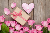 Pink roses over wooden table with valentines day gift box and he
