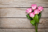 Valentines day background with pink roses over wooden table