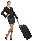 Businesswoman holding wheeled bag, hand on hip