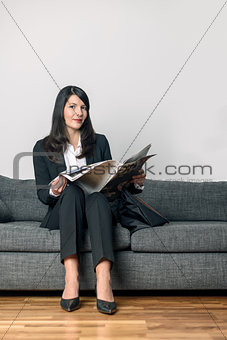 Attractive businesswoman reading a newspaper