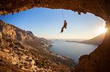 Rock climber hanging on rope while lead climbing at sunset, with Telendos island in background