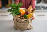 Closeup on young housewife showing fresh vegetables in shopping