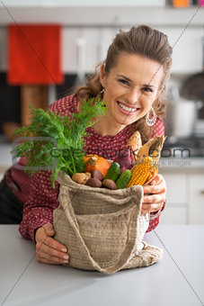 Portrait of smiling young housewife with vegetables from local m
