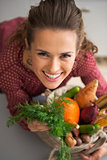 Portrait of happy young housewife with shopping bag of fresh veg