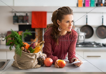Portrait of young housewife with checks after grocery shopping