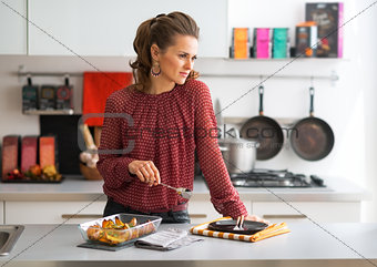 Portrait of thoughtful young housewife with pan of baked pumpkin