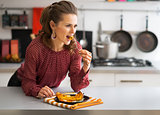 Portrait of young woman eating baked pumpkin in kitchen