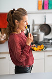 Young woman eating baked pumpkin in kitchen