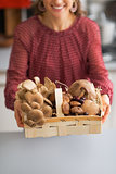 Closeup on young housewife showing basket with mushrooms