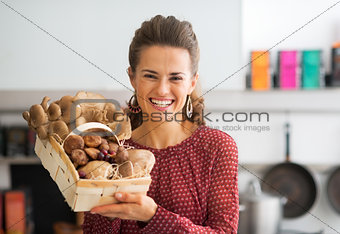 Portrait of smiling young housewife showing basket with mushroom