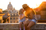 Mother and baby girl kissing while sitting on street overlooking