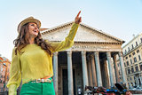 Portrait of happy young woman pointing in front of pantheon in r
