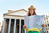 Happy young woman looking at map in front of pantheon in rome, i