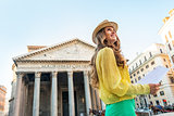 Portrait of happy young woman with map in front of pantheon in r