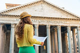Young woman looking at map in front of pantheon in rome, italy.