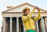 Happy young woman taking photo in front of pantheon in rome, ita