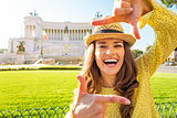 Happy young woman framing on piazza venezia in rome, italy