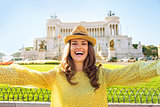 Happy young woman making selfie on piazza venezia in rome, italy