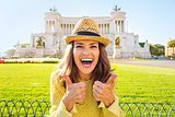 Portrait of happy young woman showing thumbs up on piazza venezi