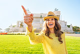 Portrait of happy young woman pointing while on piazza venezia i