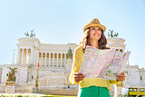 Happy young woman with map on piazza venezia in rome, italy